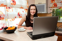 Woman with laptop in kitchen Royalty Free Stock Images