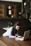 Woman on a laptop in kitchen Royalty Free Stock Images