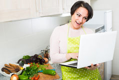 Woman with laptop in kitchen Stock Photos