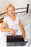 Woman with laptop laying Stock Images