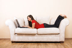 Woman with a laptop on a lounge Royalty Free Stock Images