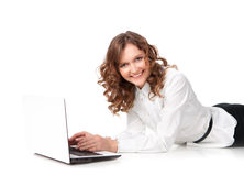 Woman with laptop lying down on the floor Royalty Free Stock Image