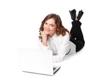 Woman with laptop lying down on the floor Stock Images