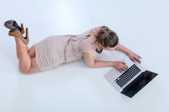 Woman with a laptop lying on the floor Stock Images
