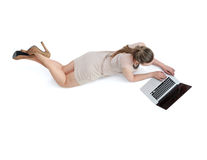 Woman with a laptop lying on the floor.  Royalty Free Stock Photography