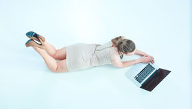 Woman with a laptop lying on the floor.  Royalty Free Stock Images
