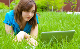 Woman with laptop lying on the grass Royalty Free Stock Images