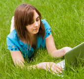 Woman with laptop lying on the grass Royalty Free Stock Photography