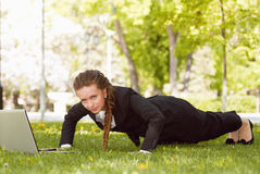 Young woman with laptop lying in the green grass Stock Images