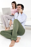 Woman with laptop and man with mobile. Woman sat on the sofa with laptop and man with mobile Stock Image