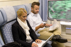 Woman with laptop man newspaper in train Stock Image