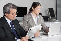 Woman with laptop and man reading Stock Image