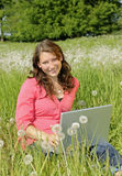 Woman with laptop on a meadow Stock Images