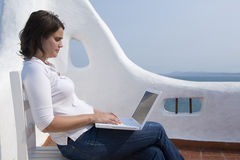 Woman with laptop in a mediterranean terrace Stock Photos