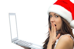 Woman with laptop notebook in christmas hat Royalty Free Stock Photos