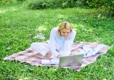 Woman with laptop or notebook sit on rug green grass meadow. Business lady freelancer work outdoors. Business picnic stock photography