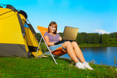 Woman with laptop outdoor. Outdoor portrait of beautiful happy woman with laptop sitting in folding chair near camp tent Stock Images