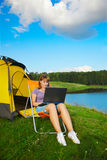 Woman with laptop outdoor. Outdoor portrait of beautiful woman with laptop sitting in folding chair near camp tent Stock Images