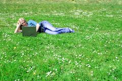 Woman with laptop outdoor. A young smiling woman is lying on a meadow with her notebook Stock Image