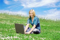 Woman with laptop outdoor. A young smiling woman is lying on a meadow with her notebook Stock Images