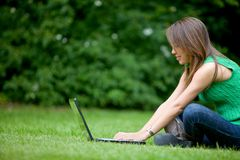 Woman with a laptop outdoors Stock Image