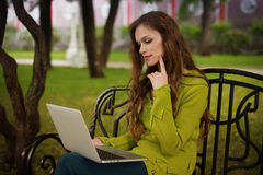 Woman with laptop in the park Stock Images