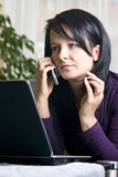 Woman on laptop and phone Stock Images