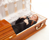 Woman with laptop and phone in coffin Stock Image