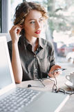 Woman with laptop and phone listening music in cafe Royalty Free Stock Photo