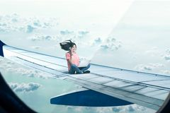 Woman with laptop and phone sitting on plane wing Stock Photo