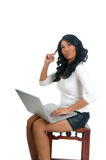 Woman with laptop pointing finger on head Stock Photo