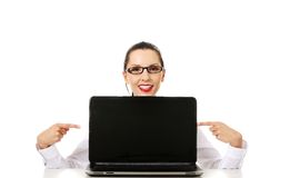 Woman with laptop points to the screen. stock photos