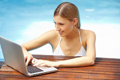 Woman with laptop in pool stock images