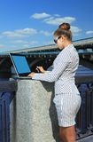 Woman with laptop on quay Stock Images