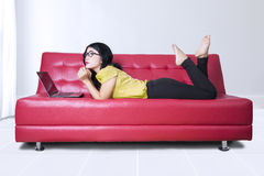 Woman with laptop on red sofa at home Stock Image