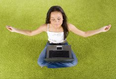 Woman with laptop relaxing on the green carpet. Young woman with laptop relaxing on the green carpet royalty free stock images