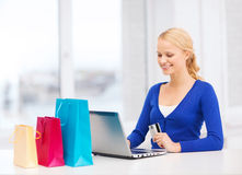 Woman with laptop, shopping bags and credit card. Christmas, x-mas and online shopping concept - smiling woman with shopping bags, laptop and credit card Stock Photo
