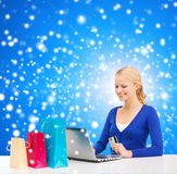 Woman with laptop, shopping bags and credit card. Christmas, x-mas and online shopping concept - smiling woman with shopping bags, laptop and credit card Royalty Free Stock Image