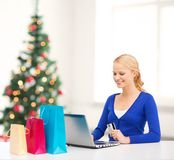 Woman with laptop, shopping bags and credit card. Christmas, x-mas and online shopping concept - smiling woman with shopping bags, laptop and credit card Royalty Free Stock Photo