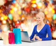 Woman with laptop, shopping bags and credit card Royalty Free Stock Image