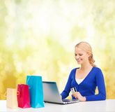 Woman with laptop, shopping bags and credit card. Christmas, x-mas and online shopping concept - smiling woman with shopping bags, laptop and credit card Stock Images