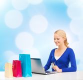 Woman with laptop, shopping bags and credit card Stock Photo
