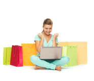Woman with laptop and shopping bags. Happy young woman with laptop and shopping bags royalty free stock photos