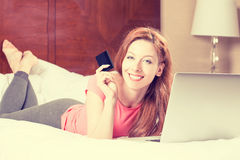 Woman with laptop shopping on line showing credit card Royalty Free Stock Images