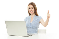 Woman with laptop showing thumbs up Stock Photo