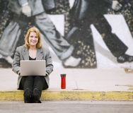 Woman with laptop on a sidewalk Stock Photos