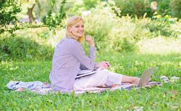 Woman with laptop sit grass meadow. Best jobs to work remotely. Business lady freelance work outdoors. Remote job. Concept. Stay free with remote job. Managing royalty free stock photography