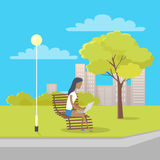 Woman with Laptop Sits on Bench in City Park Royalty Free Stock Images