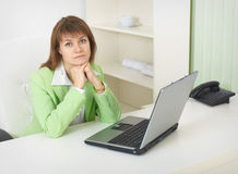 Woman with laptop sits at table at light office Royalty Free Stock Photo