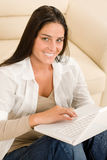 Woman with laptop sitting on couch smiling Stock Photography